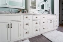 Deluxe new home features double vanity built from inset Shaker cabinets. Bathroom has dual custom mirrors, glass-front cabinet and drawer stacked on counter, and porcelain tile floor