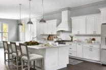 open kitchen with white shaker cabinets, large island, white wood range hood with holiday decorations