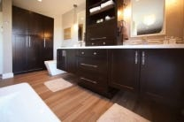 double vanity built of black shaker cabinets has floating vanity sections with drawer base between and wall of storage cabinets with bamboo floor and contemporary toilet and freestanding tub
