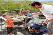 family grilling outside forest