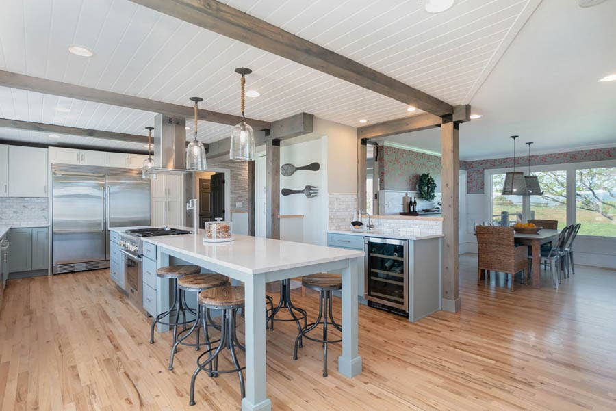Gray kitchen island with space for seating and stainless steel stove
