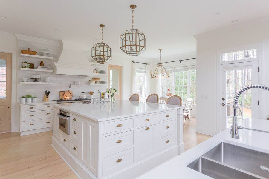 Massive custom built island with sink, microwave and specialty cabinet storage, with large glass pendant lights above