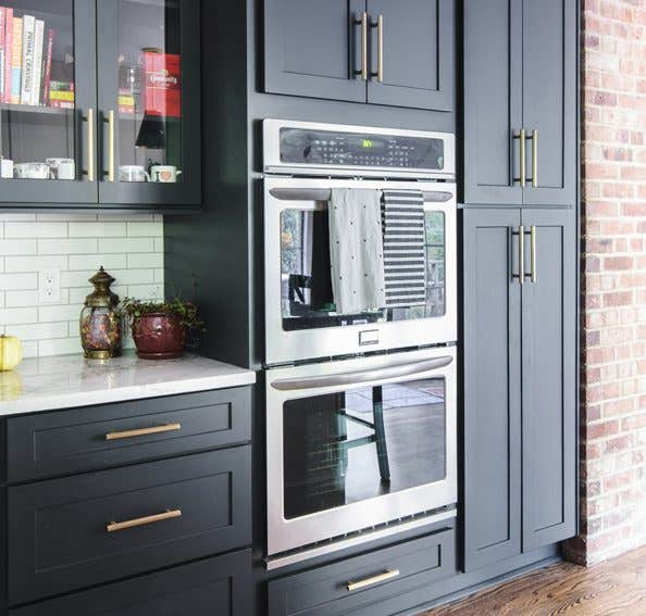 Kitchen using CliqStudios Dayton cabinets in carbon with white countertops, stainless steel double ovens, and exposed brick walls.