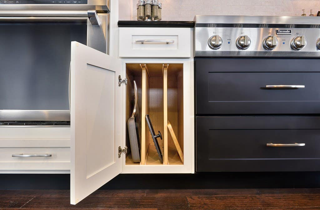 Smart storage solutions by CliqStudios keeps your kitchen organized with features such as this upright tray divider base cabinet, shown here in Dayton shaker cabinet style in painted White finish and paired with Dayton in painted Carbon finish