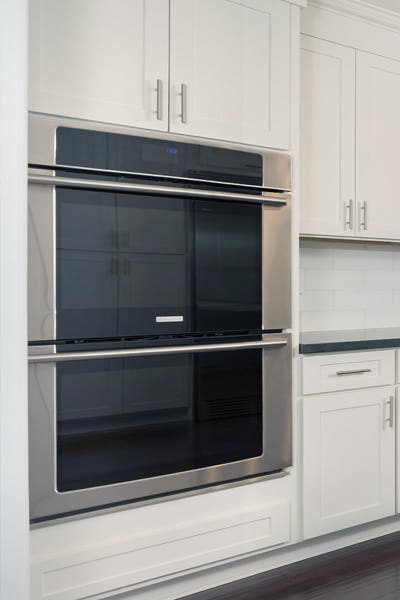 A kitchen with stainless steel double wall oven and white wall oven cabinets.