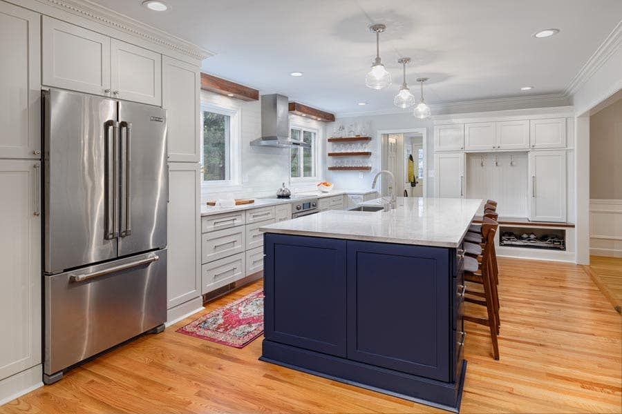 two-tone kitchen with white cabinetry and navy kitchen island