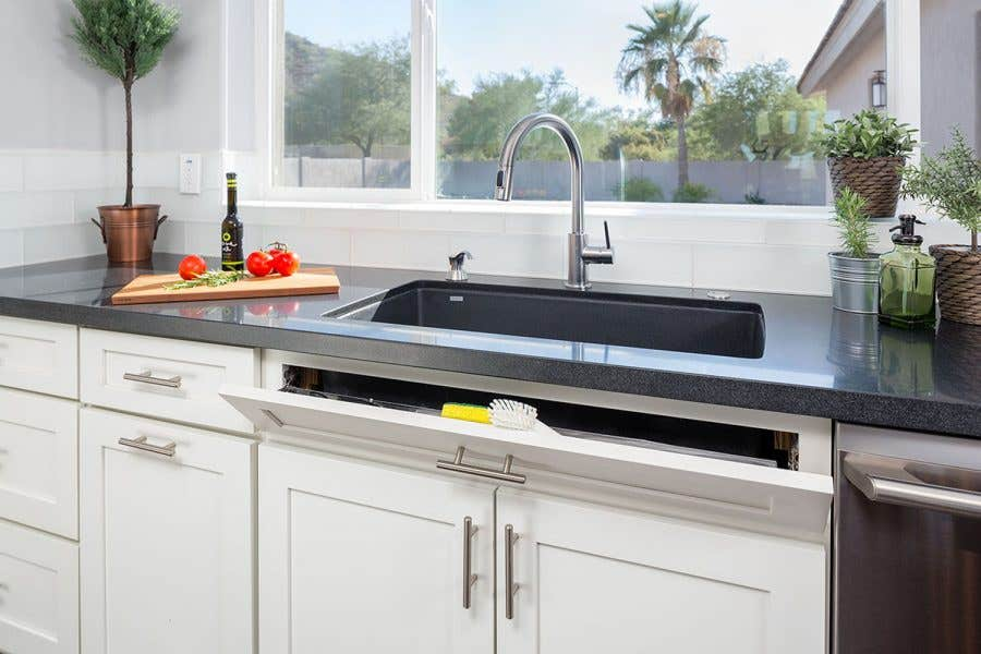 modern kitchen sink wall has large window, white shaker cabinets and sink tip out tray for small item storage and pull-out trash can.