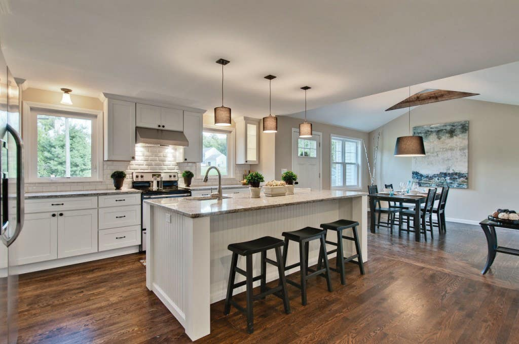 Spacious kitchen has painted white Shaker cabinets, large island with seating and a sink, opens to dining room