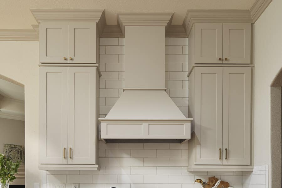 CliqStudios wood range hood in light gray paint called Urban Stone installed with tall wall cabinets on either side.