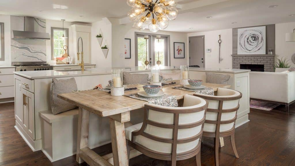 A kitchen using CliqStudios Rockford cabinets in white, with banquet seating built in to the islan