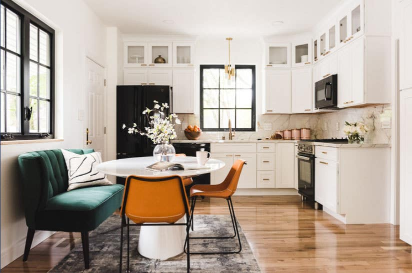 cloud white shaker cabinets with black appliances, marble backsplash and glass front doors by ceiling