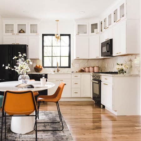 cloud white kitchen with black appliances opens to dining area with white table and burnt orange chairs