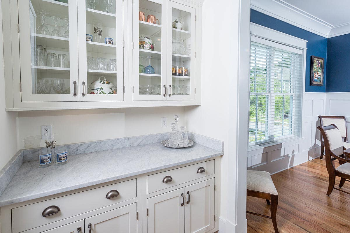 view through the butlers pantry into the adjacent dining area, where the white painted, shaker style architectural style continues with board and batten paneling and wide baseboard