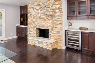 stone fireplace surround includes cherry cabinets, glass doors, open shelves and dry bar