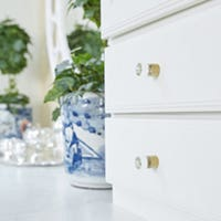 CliqStudios Bayport cabinets in White with glass knobs. Next to the cabinets is a plant in a blue and white china pot.