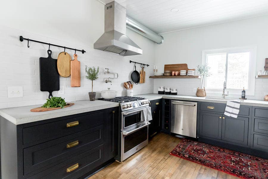 A rustic modern kitchen using black, inset cabinetry and modern square cup pulls