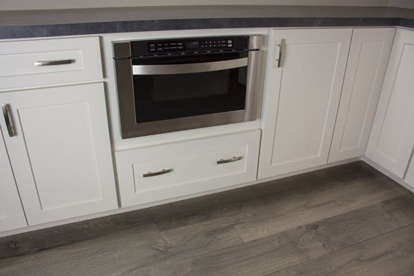 Microwave shelf with a gray countertop and gray flooring.