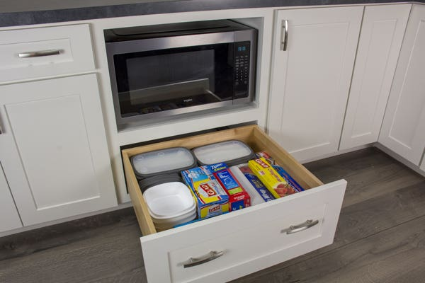Open white drawer under a microwave shelf filled with food storage supplies
