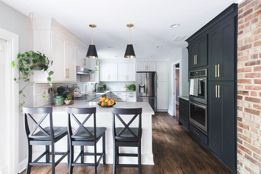 Without major layout changes, this kitchen was transformed with a pantry wall and polished black and white cabinets