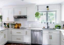 A white kitchen using CliqStudios Dayton cabinets, with white subway tile backsplash and countertop.