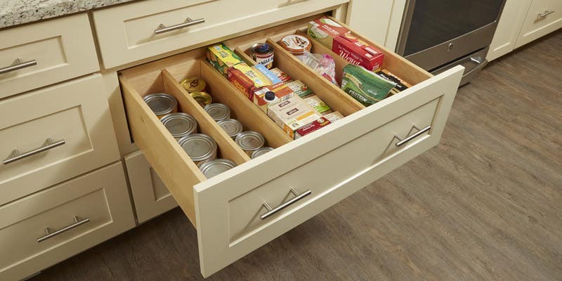 CliqStudios Dayton Cabinet in Painted Linen Multi-Storage Drawer cabinet. Drawer has wooden dividers and is filled with food