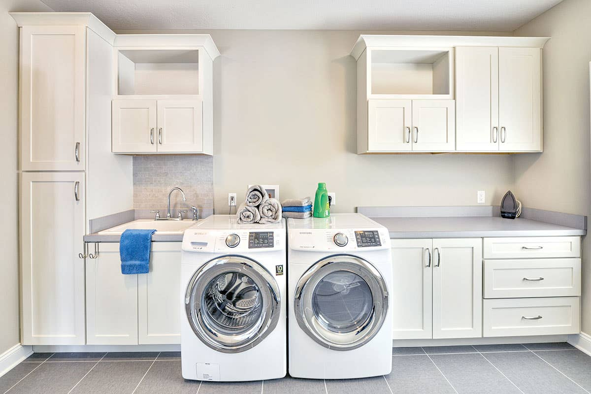 white laundry cabinetry washing machines sink drawers shelves utility