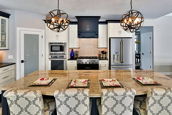 Two toned black and white kitchen with kitchen island and hanging pendant lights