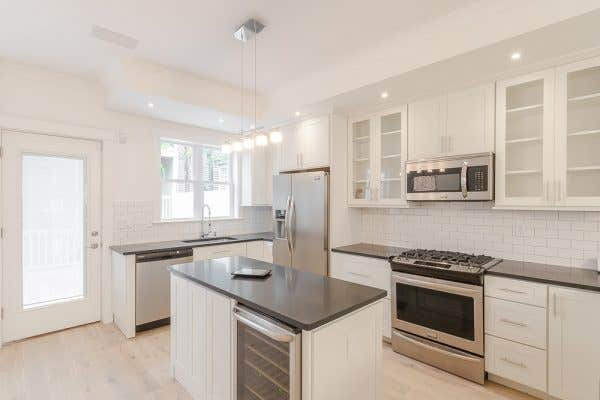 Boston, Massachusetts, home features remodeled with with painted white cabinets, bleached wood floors, built-in beverage cooler in the island, modern island chandelier and six-burner gas range.