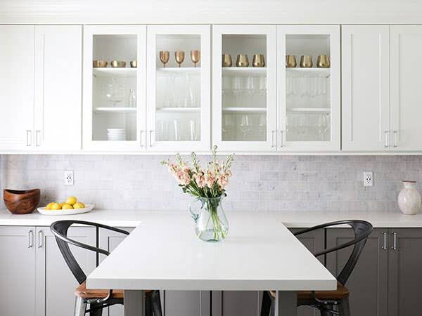 Two-toned cabinets in Dayton White and Studio Gray, with a white peninsula dining area featuring a vase of flowers and glass cabinet doors showing clear glasses and bronze cups