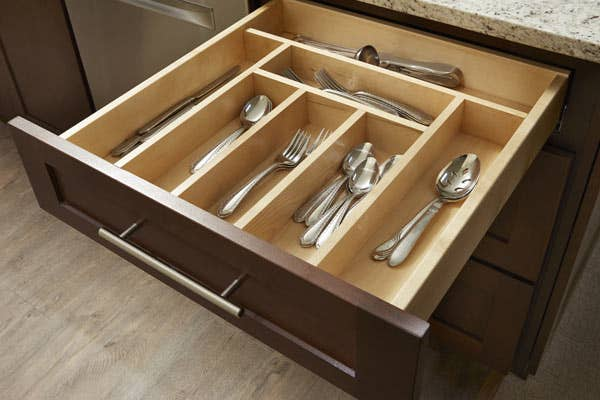 A silverware drawer insert in a CliqStudios drawer. Inside are spoons, forks, and knives.