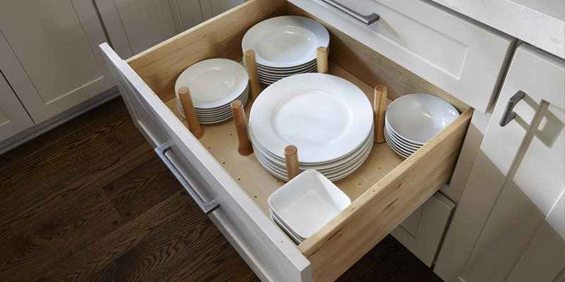 A CliqStudios peg drawer, using wooden pegs to organize dishes.