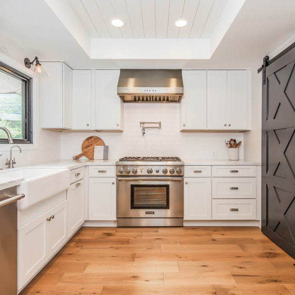 White kitchen with shaker cabinets barn door and stainless appliances