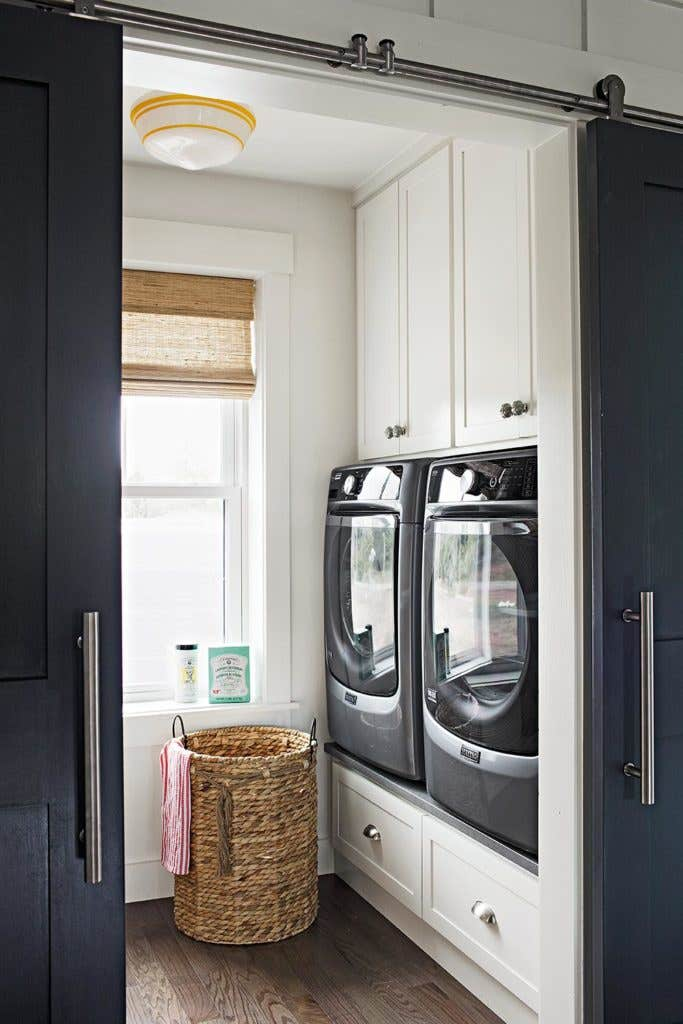 white laundry room cabinetry raised drawer storage sliding doors woven basket
