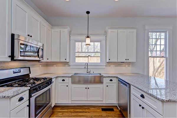 White U-shaped kitchen layout with stainless steel sink and a single hanging pendant