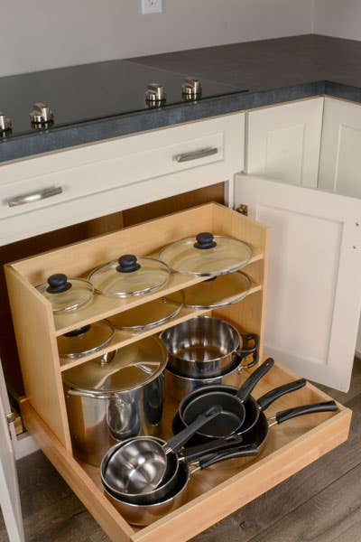 Pots and Pans pullout organizer, filled with pots and pans on the lowers roll out tray, and lids on the 2 shelves.