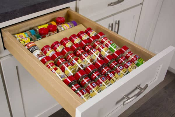 A drawer with a spice drawer insert, filled with spices.
