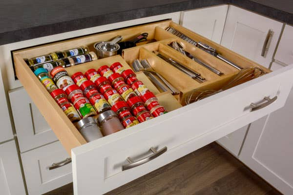 Drawer with a full spice drawer insert and a full silverware insert, side by side.
