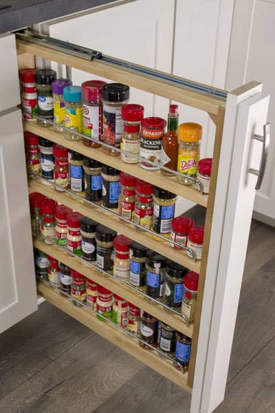 Pull-out storage cabinet with three shelves storing spices and seasonings.