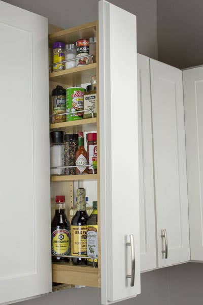 Pull-out storage cabinet with three shelves storing spices and other small assorted jars.