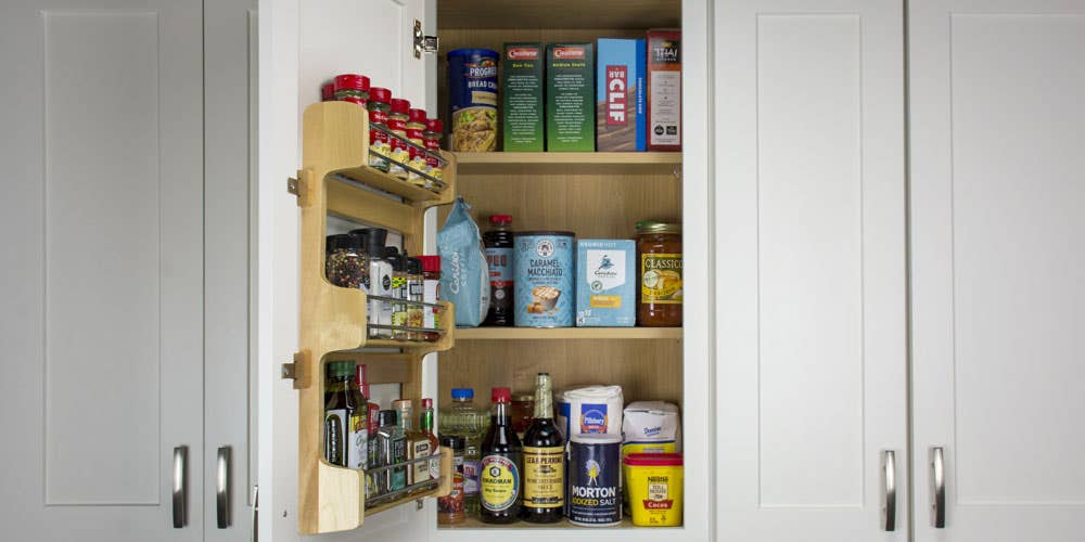 door mounted spice rack placed on the inside of a cabinet.