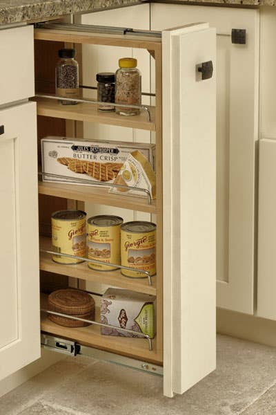 Base pull-out storage cabinet with three shelves storing cans, crackers, tea, and herbs