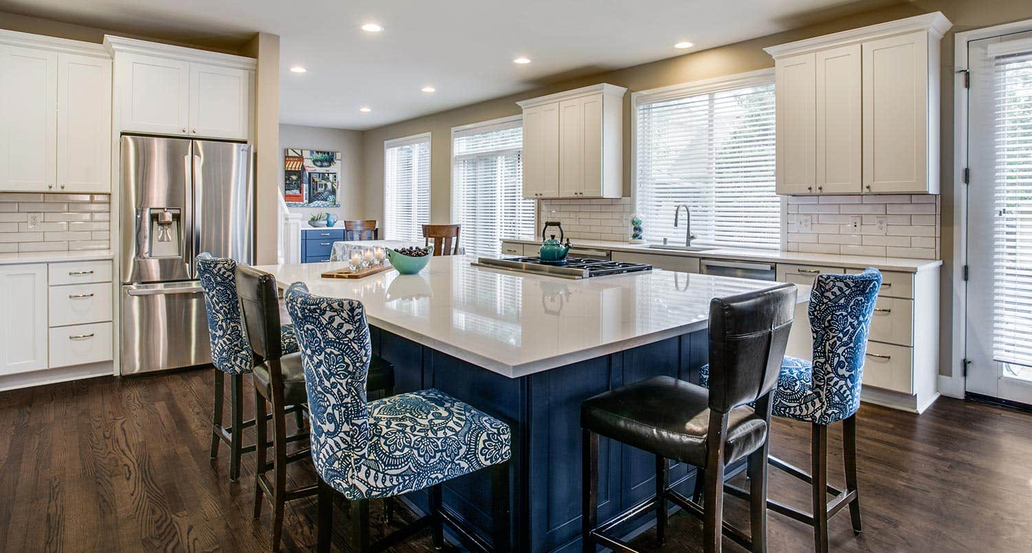 large navy island surrounded by blue chairs and installed white kitchen cabinets