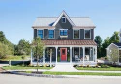 Outside of a blue and white two story house with front porch and red front door