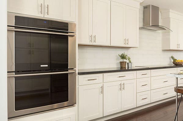 kitchen has double wall ovens in white shaker cabinets and glass cooktop on black granite countertop below glass range hood