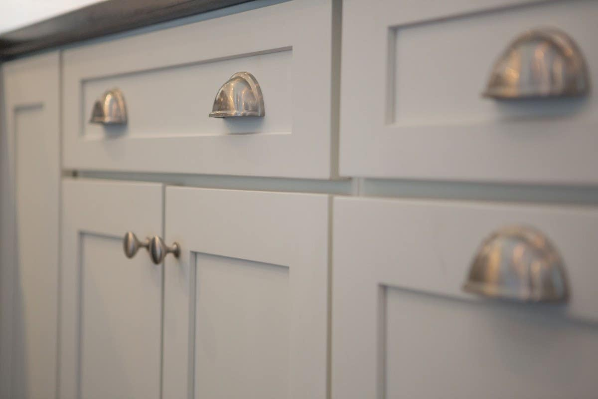 Cup pulls are often combined with a coordinating knob. The cup pull is used on the drawer, and the knob is used on all doors and upper cabinets.