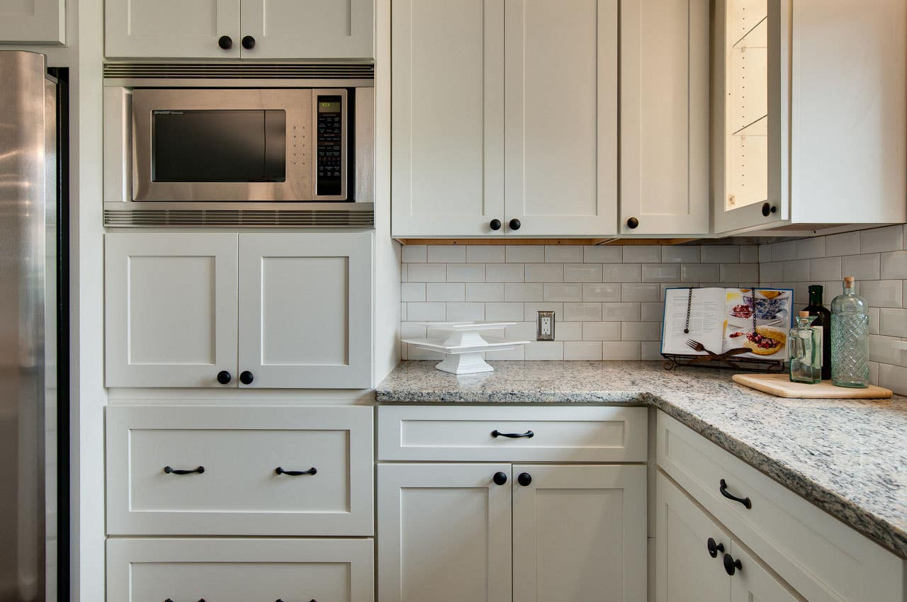 inside corner of kitchen has painted white cabinets in a shaker style with oiled brass pulls and knobs, granite countertop and built in microwave
