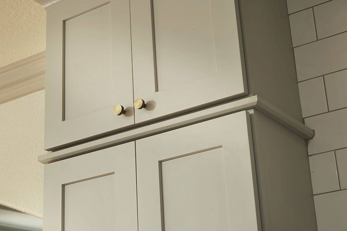 aged brass knobs on light gray shaker cabinets