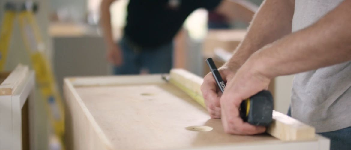 Picture of a kitchen cabinet installer running a tape measure across the top of an upper cabinet