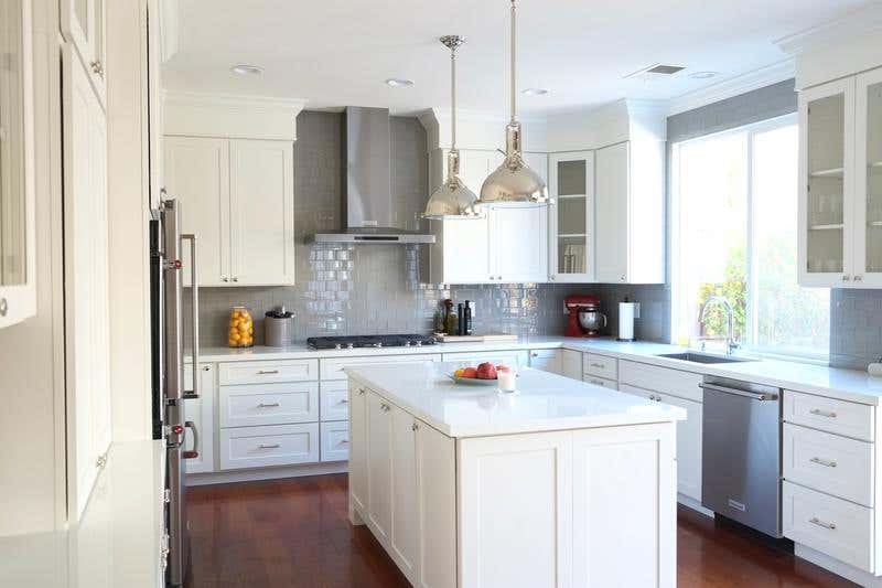 shaker style cabinets in white with pendant lights and a kitchen island