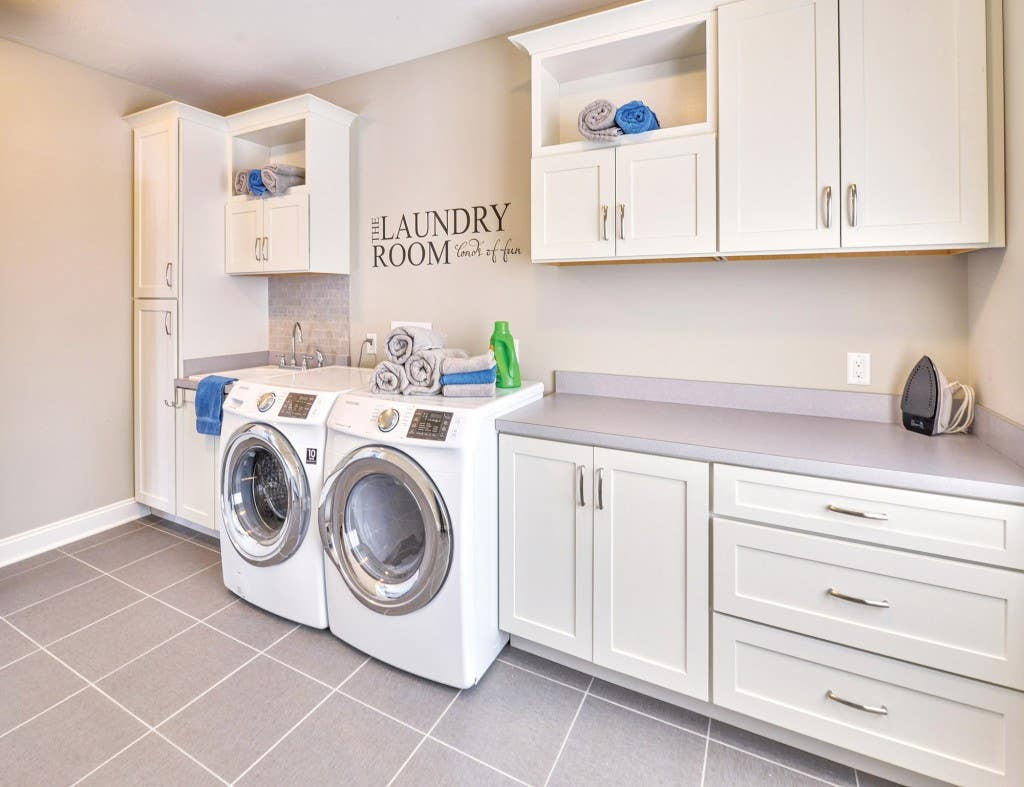 Spacious and bright laundry room custom built with CliqStudios.com shaker style cabinets. Shown Dayton shaker cabinet style in painted White finish.